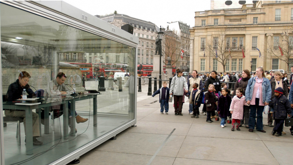 Two performers in a glass structure act out a conceptual work of art by On Kawara in Trafalgar Square in 2004.